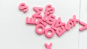 pink letters laid out for learning how to play hangman
